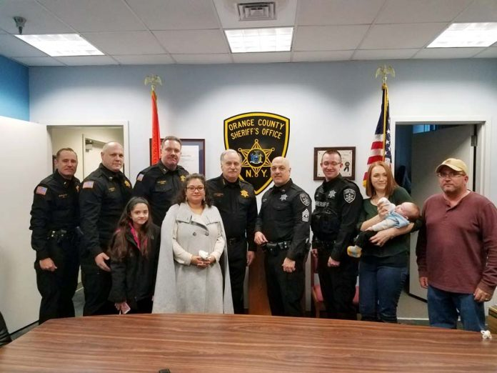 From Left to Right: Lt. Kevin Williams, Capt. Paul Arteta, Chief Dennis Barry, Sheriff Carl DuBois, Lt. Larry Cottone, Sgt. William Cluney and Sgt. Cluney's family pose for a photo.