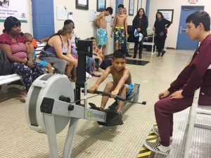 Anthony is on the ergometer, learning to row during the open house.