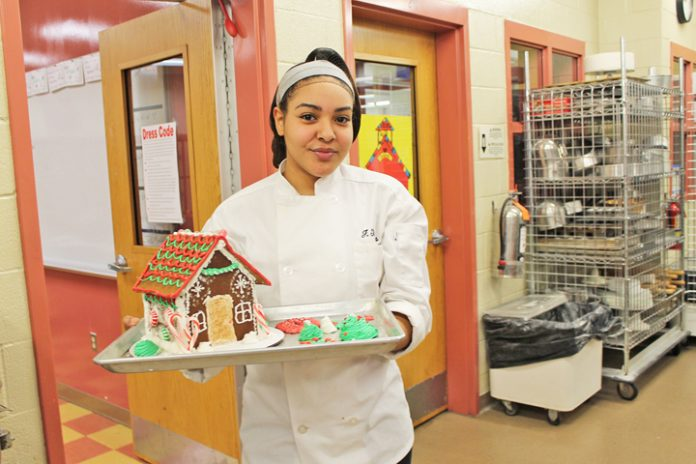 Culinary Arts student Faith Thomas from the Kingston City School District shows off the gingerbread houses her class made for a raffle. Proceeds from the raffle will go to Toys for Tots. Photo: Tammy Cilione