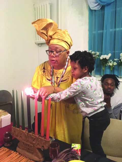 "Pamela Woodard assists the youngest member in attendance at Friday's Black History Committee's Annual Kwanzaa Celebration light the candles, as the day's Principle, ""Ujima"" (Collective Work and Responsibility) was celebrated."