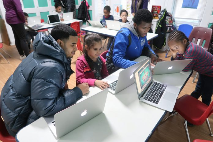 Andres Carpio, HEOP academic counselor at the Mount (left) and a Mount student (right) mentor young children at the Newburgh Boys and Girls Club recently. Photo: Matt Frey