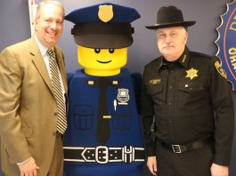 """District Attorney David Hoovler (left) and Sheriff Carl E. DuBois (right) with LEGOLAND New York's """"Police Officer Parks"""" outside of Hoovler's office at the Government Center."""