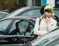 Woman deciding a car purchase in dealer lot.