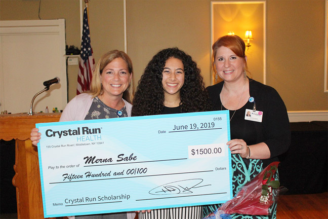 Crystal Run Healthcare Scholarship Award winner Merna Sabe (center) accepts her check from Crystal Run Healthcare's Marketing Manager, Lynn Haskin (right) and Director of Human Resources, Tara Kammarada (left), at the Middletown BPW's scholarship dinner on Wednesday, June 19th.