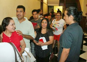 Acevedo, right, chats with Newburgh residents waiting on line to be issued their municipal ID cards.