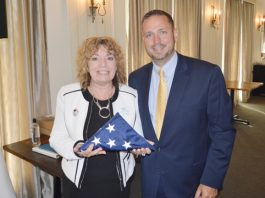 Steven Neuhaus, Orange County Executive, presents Lynn Allen Cione, President and CEO of the Orange County Chamber of Commerce, with an American flag that was flown in Baghdad at the Headquarters of the CJSOTF (Combined Joint Special Operations Task Force) during his deployment on Thursday, July 11, 2019.