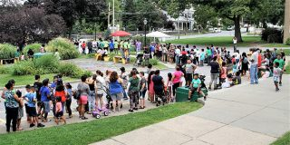 Long line of students and parents at the Family Partnership Center for the back-to-school backpacks.