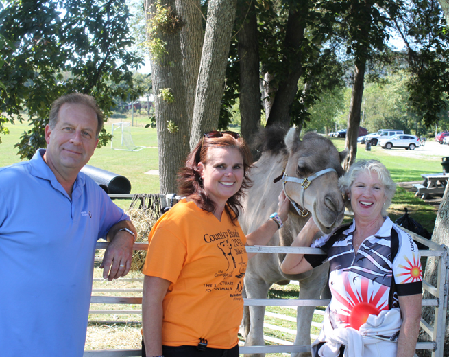 Anthony Gillmeier, Big Brothers Big Sisters Board Member, Kristin Jensen, Catholic Charities Chief Advancement Officer, and Peggy Cullen, Orange County Bicycle Club President, posed for a picture with the Country Roads Charity Bicycle Tour's camel mascot, Martin, who greeted riders at Warwick Town Park.