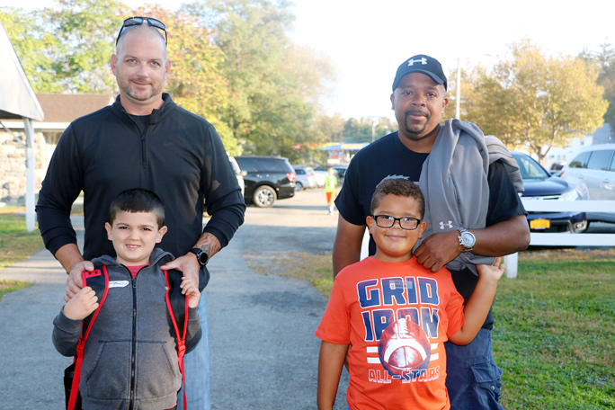 Ostrander Elementary School Grade 1 students Anthony Daly (left) and Tyler James were joined by their fathers, Jim Daly and Douglas James, for their school's celebration of National Walk to School Day.