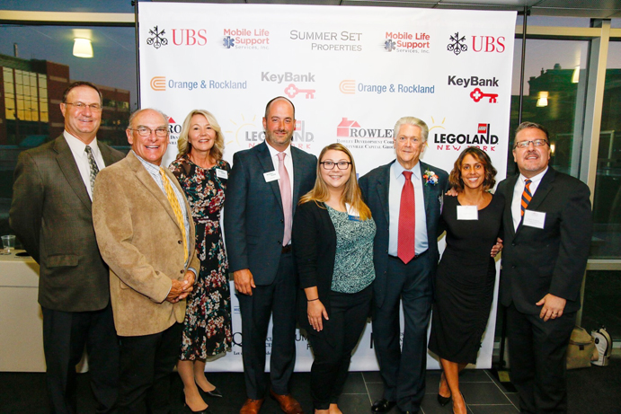 """Dr. Peter Masci, Board Director; Jeffrey Crist, Chairman of the Board; Joann Menendez, Vice President, Corporate Secretary; Greg Roe, Vice President, Commercial Lender; Abigail Doyle, Executive Assistant; William """"Bill"""" Vacca, Vice President, Business Development; Martha Soto, Branch Manager; and Derrik R. Wynkoop, President & CEO pose for a photo."""