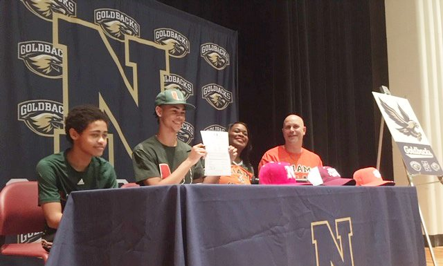 Newburgh Free Academy senior track and field standout hurdler, Ryler Gould, officially signs a letter, committing to his collegiate selection, The University of Miami, where he earned a full athletic scholarship, beginning in the fall of 2020. His younger brother Rayden along with father Rich look on. Also joining him on the stage was his mother Michelle during Monday's well-attended event at NFA's North Campus.