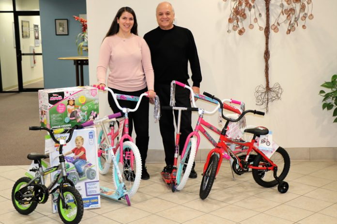 Wayne Winkler, President and CEO of Mid-Hudson Valley Federal Credit Union (MHV), is joined by Caroline Falk, Marketing Specialist at MHV, in making a donation to the Greater Hudson Valley Toy Drive.