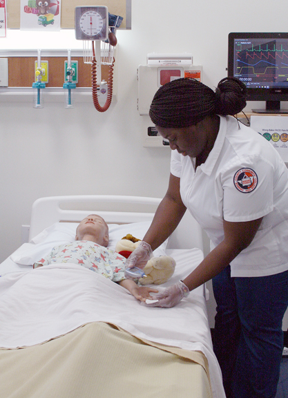 """SUNY Orange nursing student Edna Aboagye applies a finger stick to Pediatric Hal, the new state-of-the-art simulation manikin acquired by the College to enhance its nursing curriculum and training. In partnership with the SUNY Orange Foundation, the College added Hal to its simulation """"family"""" as a way to provide enhanced training to its nursing students and to overcome a shortage of available local pediatric clinical sites for current students. SUNY Orange's nursing program was founded in 1952 as the first two-year nursing degree program in the nation and has maintained a standard of excellence for nearly 70 years."""
