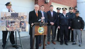 Center Charles Schumer, at the podium, is surrounded by law enforcement and county officials in KIngston.