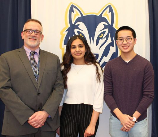 Two Highland High School (HHS) students—seniors Minh Tran and Ishani Bansal were named finalists by the National Merit Scholarship Corporation (NMSC) for the National Merit Scholarship, a prestigious award given to the nation's top students. Pictured are Minh and Ishani together, with principal William Zimmer.