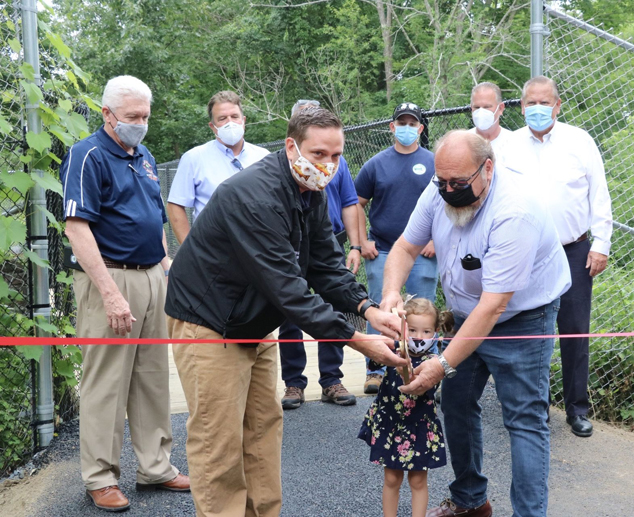 Orange County Executive Steven M. Neuhaus cuts a ceremonial ribbon to celebrate the completion of the trailhead access to the Heritage Trail in Harriman with Harriman Mayor Stephen H. Welle and Welle's granddaughter, Isabella Bruno, 2.