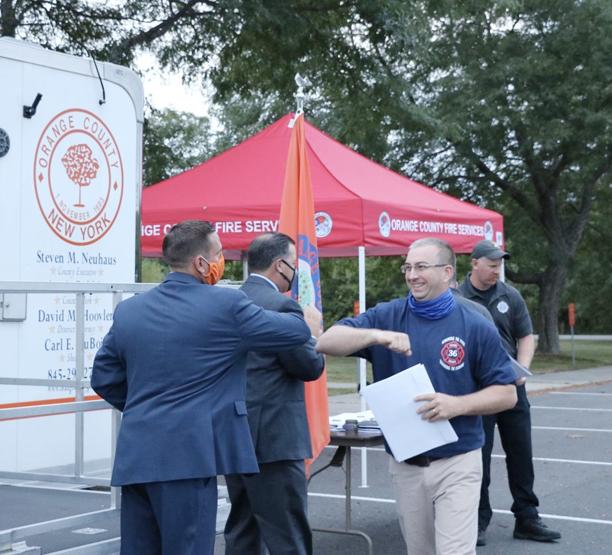 Orange County Executive Steve Neuhaus congratulates graduate William Duschaneck of the Maybrook Fire Department.