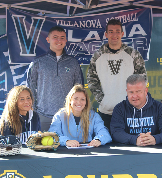 Elaina Wagner signs her National Letter of Intent as her parents, Vicki and Bill and brothers Billy and Johnny look on.
