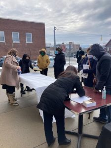 People at one of several booths available outside of 280 Broadway last Wednesday morning offer assistance to visitors. The event featured the announcement of a powerful partnership among three area organizations, allowing for a far greater breadth and frequency of area pop-up, drive-thru food pantries.