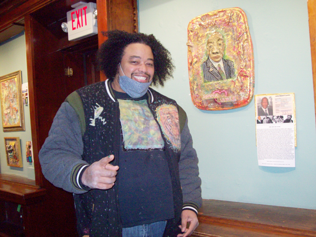 Newburgh artist, Eddison E. Romeo stands alongside a piece he is incredibly proud to have contributed to The Annual African-American Group Art Show at Howland Cultural Center. It is a three dimensional, creatively constructed caricature of Civil Rights icon, John Robert Lewis, which includes a poem Romeo crafted, paying tribute to the dynamic, game-changing Congressman.
