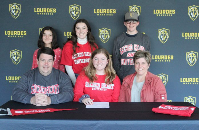 Lizzie Lyons signs her National Letter of Intent as her parents, Kathy and Peter, brother Charlie and sisters Abby and Molly, look on. Lizzie Lyons started rowing her freshman year and is now, as a senior, racing as a single at Our Lady of Lourdes High School.