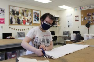 Candace VanTassell, an Ulster BOCES Fashion Design & Merchandising student from the Kingston City School District, carefully cuts fabric for the clothing she is creating for an exhibit at the Reher Center for Immigrant Culture and History.