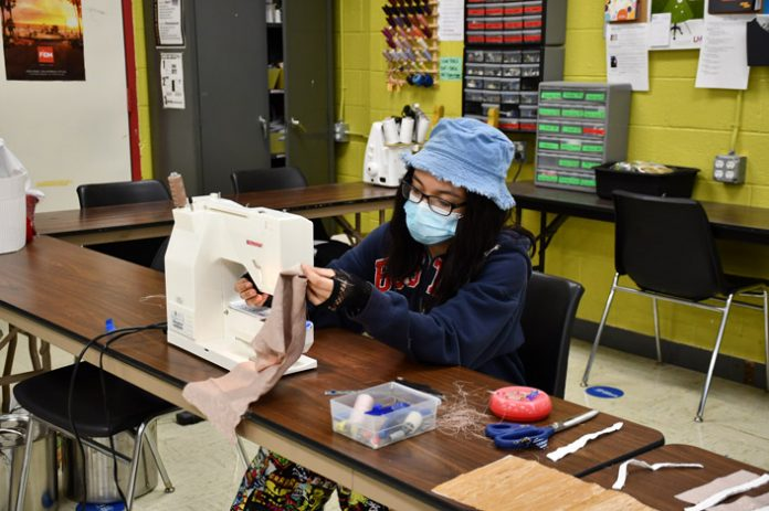 Ulster BOCES Fashion Design & Merchandising student Aliyah Follini, from the Highland Central School District, pays attention to detail as she sews fabric for clothing that represents one of nine female garment workers who worked at the Jacobson and Sons Shirt Factory in Kingston during World War I.