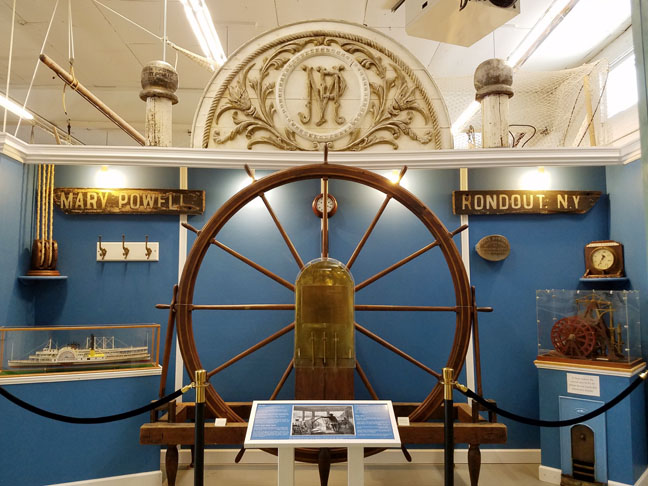 The museum's exhibit Mary Powell: Queen of the Hudson features many surviving artifacts of the decommissioned steamboat Mary Powell, including her pilot wheel, on loan from Senate House State Historic Site.