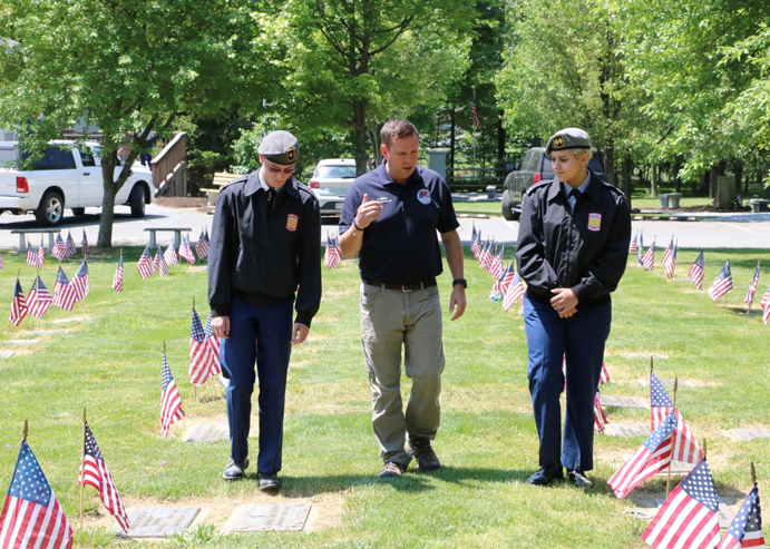 Orange County Executive Steven M. Neuhaus speaks to Minisink Valley seniors Aidan Freda and Elyssa Romero at the County's Veterans Memorial Cemetery.