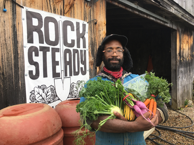 Kyle Ellis, a farmer at Rock Steady Farm in Poughkeepsie, shows off some of the beautiful, colorful bounty produced at the cooperative worker location.