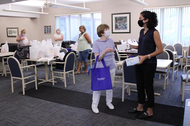 Skoufis Staff Member Yasmine Bouachri (right) donates facemasks to Meals on Wheels of Greater Newburgh President Carole S. McDermott.