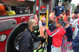 Anthony Carubia, a first lieutenant with the Modena Fire Department, talks to Plattekill Elementary School students about fire safety during the school's Health and Safety Fair, which took place on October 5, during National Fire Prevention Week. Looking on intently, from left to right, are Kindergarten students Gareth Deck, Lukas Nordahl, and Angel Delgado. Photo: Valerie Havas/Ulster BOCES Community Relations