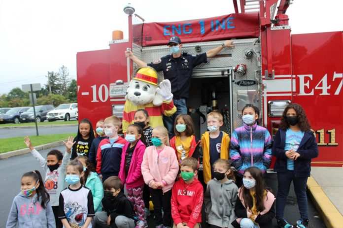 Keith Way, a firefighter with the Plattekill Fire Department, poses for a photo with Plattekill Elementary School students during the school's Health and Safety Fair, which took place on October 5, during National Fire Prevention Week.